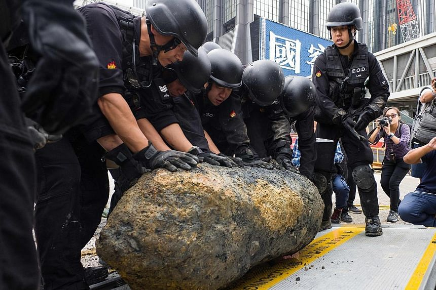 Bomb disposal officers rolling the defused World War II-era bomb into a lorry. It was the third such discovery in Hong Kong this year.