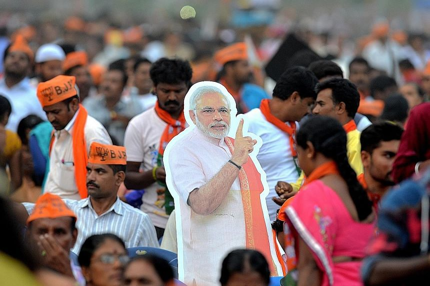 BJP supporters, with a cut-out of Prime Minister Narendra Modi, at a rally in Bangalore, near Karnataka, last week. Above: Congress president Rahul Gandhi in Malur, Karnataka, on Monday.