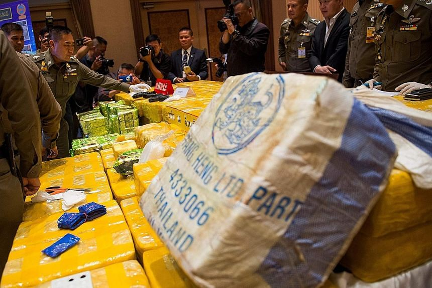 National police chief Chaktip Chaijinda (second from left) inspecting seized drugs and guns during a press conference in Bangkok yesterday.