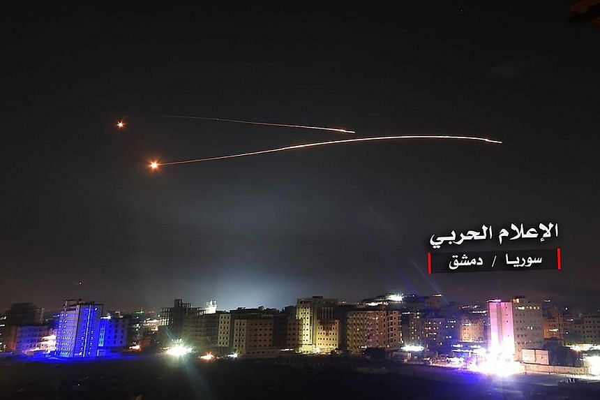 A photo released by Syria purportedly showing Syrian air defence systems intercepting Israeli missiles over Damascus airspace. An alleged Syrian missile launcher (above) being targeted by an Israeli air strike at an undisclosed location on Thursday,