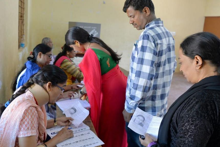 Indian voters queue to cast their ballots in the Karnataka Legislative Assembly Elections at a polling station in Bangalore on May 12, 2018.