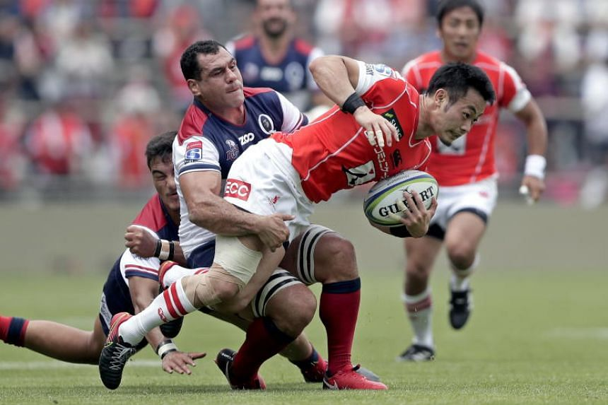 Kenki Fukuoka (right) of the Sunwolves is challenged by Jordan Petaia (left) and George Smith (centre) of the Reds during their Round 13 Super Rugby match at Prince Chichibu Memorial Stadium in Tokyo on May 12, 2018.