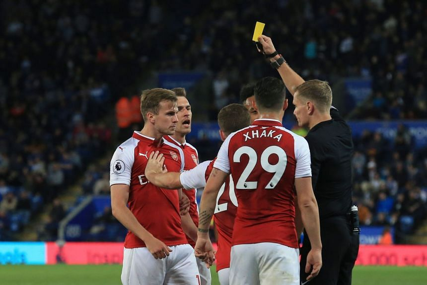 Referee Graham Scott shows a yellow card to Arsenal's Rob Holding (left).