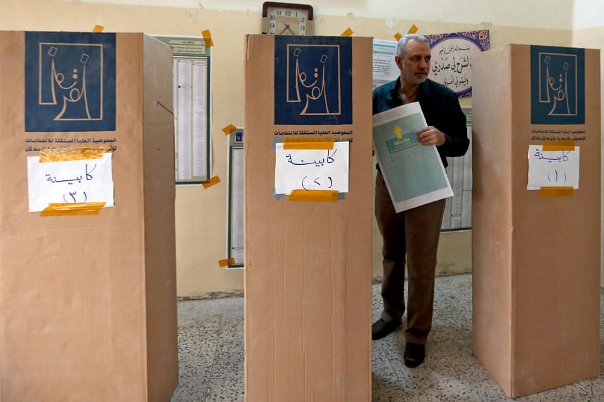 A man prepares to vote during the Iraqi legislative election at a polling station in Baghdad, on May 12, 2018.