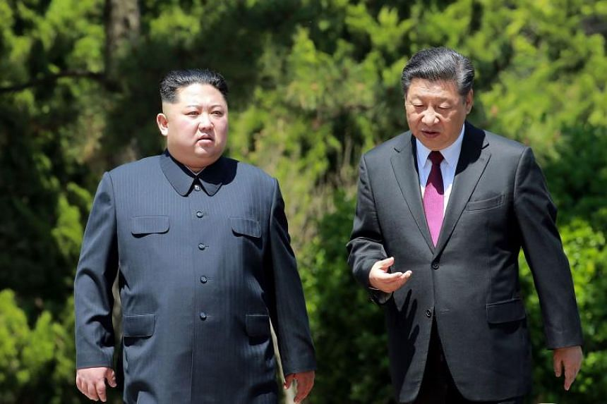 China's President Xi Jinping (right) walking with North Korean leader Kim Jong Un in the Chinese city of Dalian, on May 8, 2018.