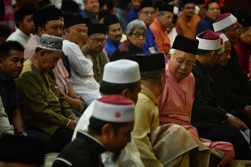 Former Malaysian prime minister Najib Razak (front row, in pink) at evening prayers at Umno's headquarters yesterday. The party marked its 72nd anniversary in a subdued manner after a bruising defeat at the polls. Several Umno leaders have called for