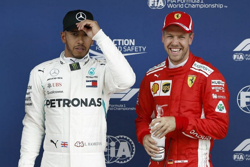Hamilton (left) celebrates after winning the pole position aside of third-placed Vettel.