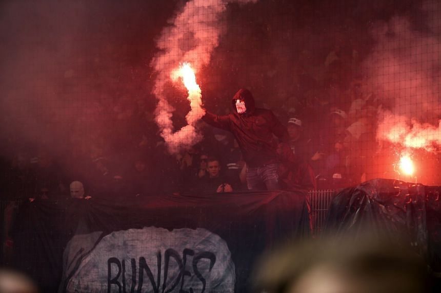 Hamburg's fans light flares at the end of the match.