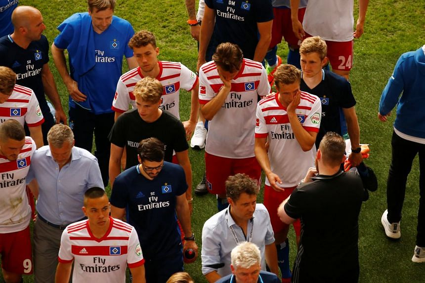 Hamburg players look dejected as they leave the pitch at the end of the match.