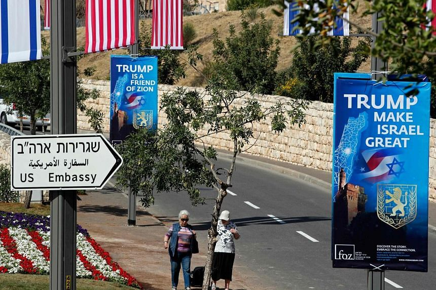 Passers-by near the new United States embassy in Jerusalem, as banners praising President Donald Trump hang from lamp posts along the streets.