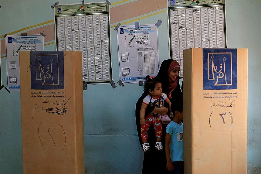 An Iraqi woman voting at a polling station in the Sadr city district of Baghdad yesterday. The winner of the election will have to deal with geopolitics, sectarian divisions, economic hardship and corruption in the country.