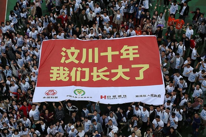 """Quake orphans, raised in Ankang Jiayuan, back at the welfare home last Wednesday to mark the 10th anniversary. Their banner reads: """"Ten years after the Wenchuan earthquake, we have all grown up."""""""