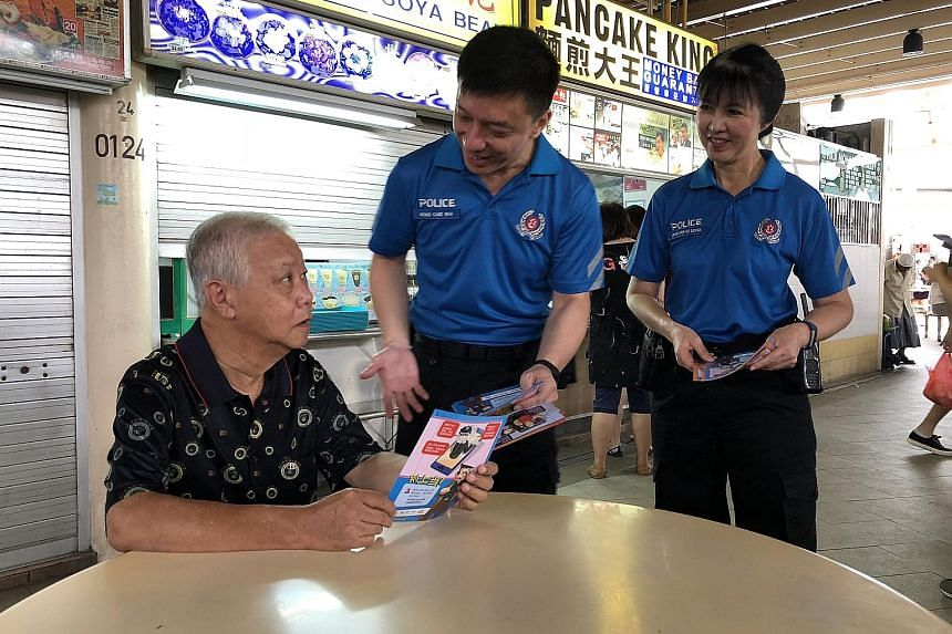 VSC (Community) officers Wong Chee Wai and Lena Wan chatting with retired transportation officer Lee Kim Seng while distributing leaflets on online scams at Serangoon Garden Market and Food Centre yesterday.