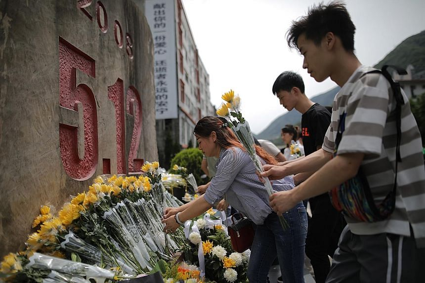 A remembrance ceremony (above) was held yesterday at a collapsed school in the town of Yingxiu, one of the worst-hit areas in the Sichuan quake. In Beichuan county (below), visitors offered flowers to mourn the victims.