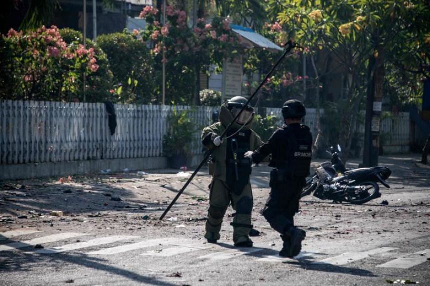An Indonesian bomb squad examines the site following a suicide bomb outside a church in Surabaya on May 13, 2018.