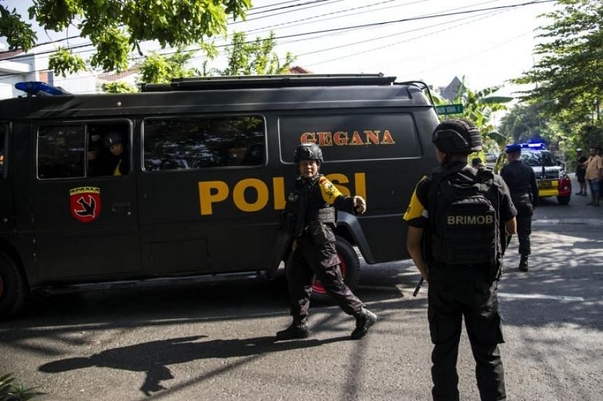 Indonesian policemen patrol outside a church following a suicide bomb in Surabaya on May 13, 2018.