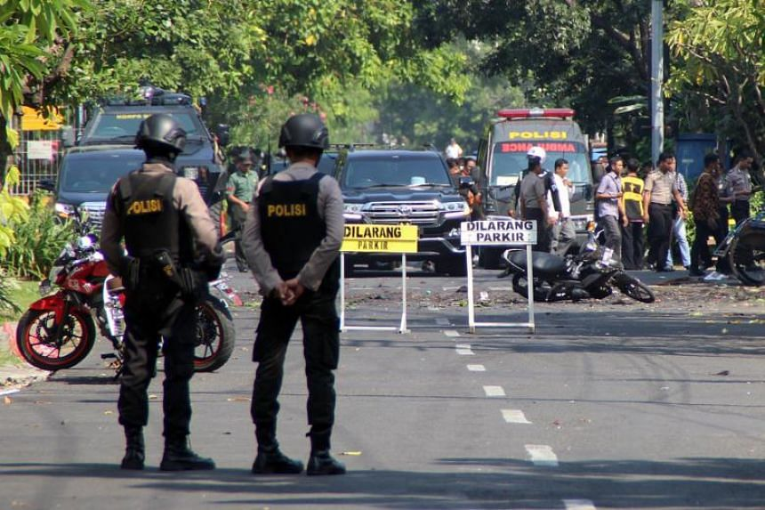 Indonesian bomb squad police officers inspect a blast site in front of a church in Surabaya, Indonesia on May 13, 2018.
