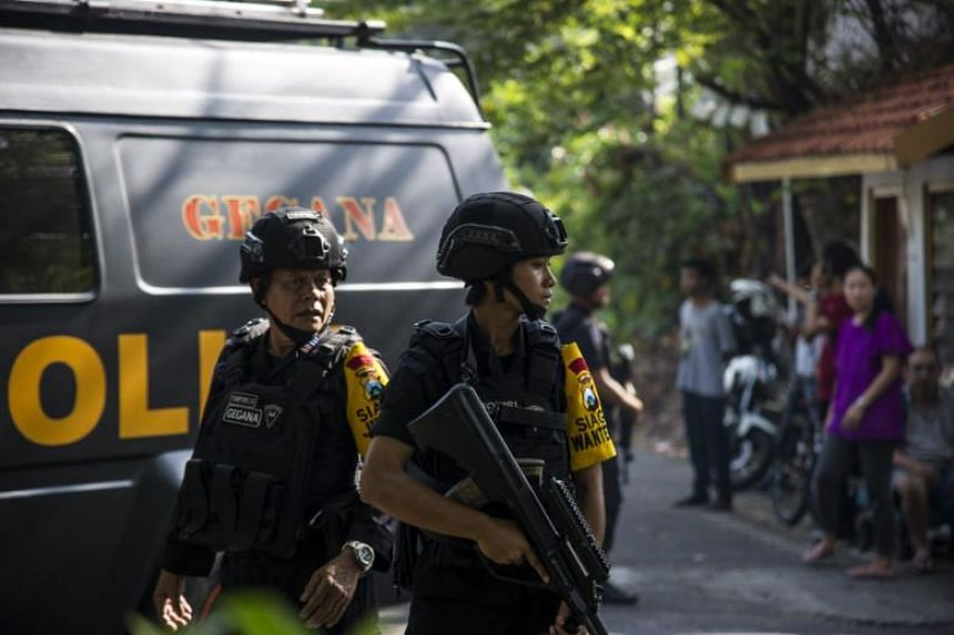 Indonesian policemen patrol outside a church following a suicide bomb attack in Surabaya on May 13, 2018.