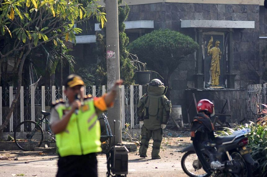 A member of the police bomb squad unit examines the site of an explosion outside the Immaculate Santa Maria Catholic Church, in Surabaya, Indonesia on May 13, 2018.