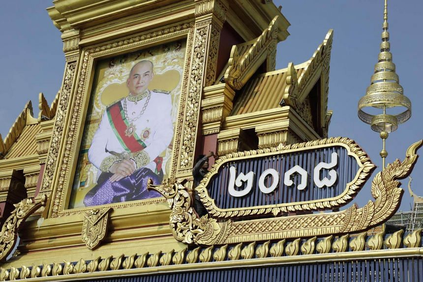A man working next to a large portrait of Cambodia's King Norodom Sihamoni in front of the Royal Palace in Phnom Penh on May 12, 2018.