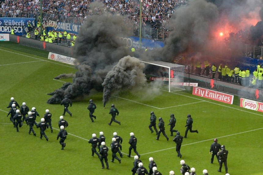Fireworks burn and police officers run onto the pitch ahead the final whistle.