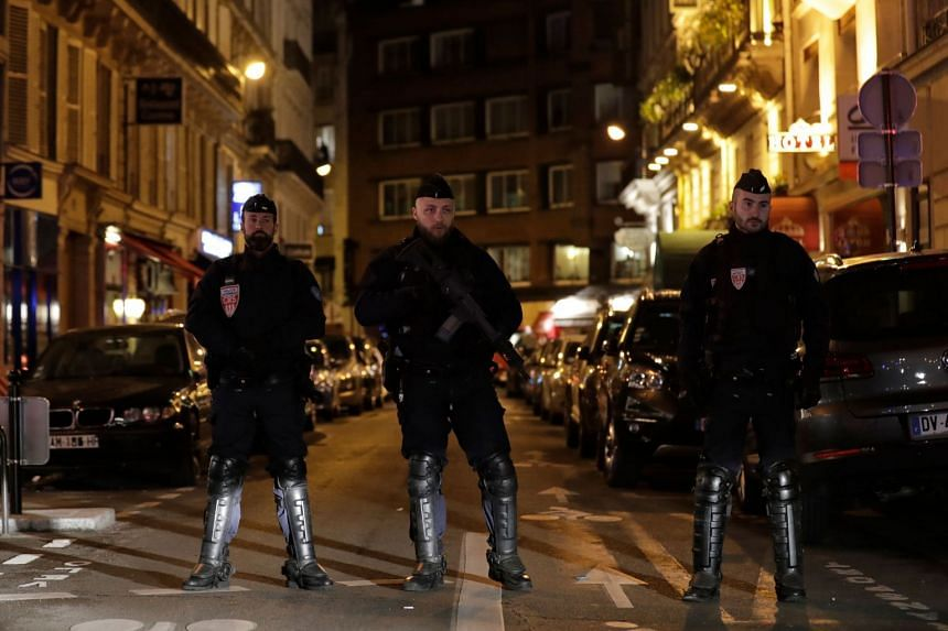 Police stand guard in Paris after a person was killed and several injured in a knife attack.