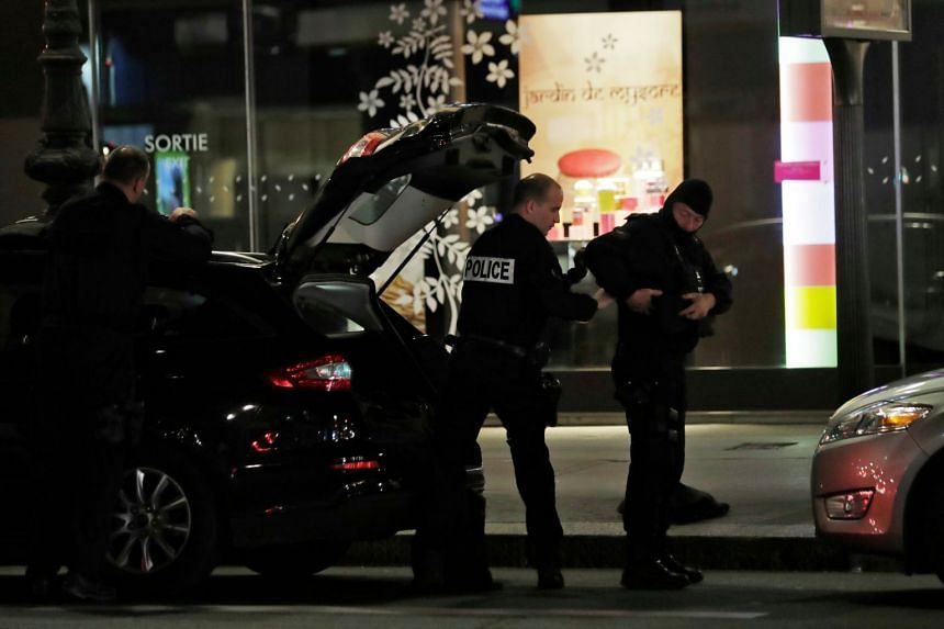 Police put their gear on in Paris after a person was killed and several injured by a man armed with a knife.