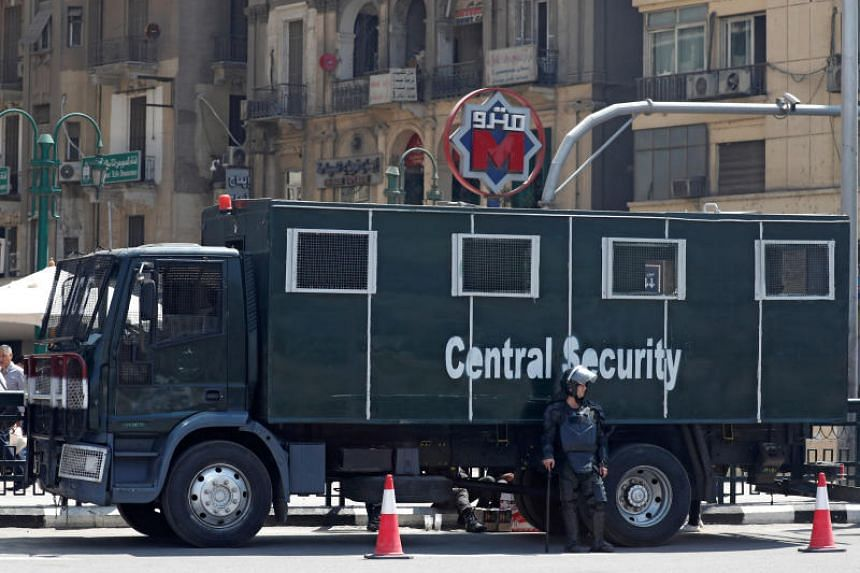 An Egyptian riot police officer and riot vehicle is seen outside El Sadat metro station at Tahrir square in Cairo on May 13, 2018.