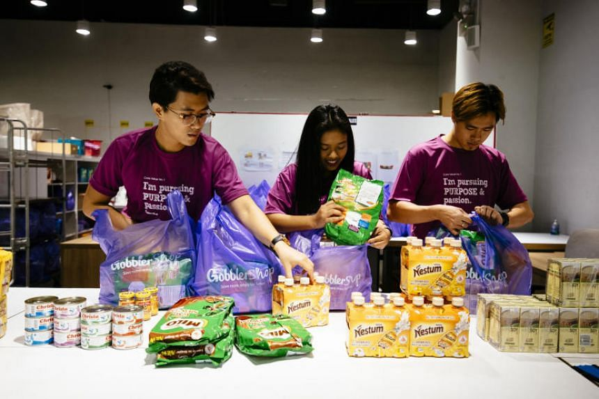 (From left) Mr Ephraim Teng, Ms Nurul Fatehah and Mr Sean Soo packing grocery packs as part a partnership between Halal Goods Do Good and GobblerShop for Ramadan.