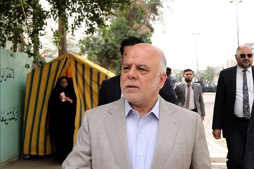 Iraqi PM Haider al-Abadi arriving at a polling station to cast his vote, in Baghdad on May 12, 2018.