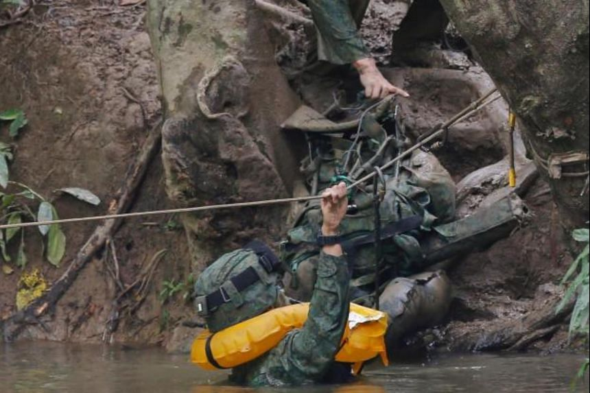 SAF officer cadets crossing a river using a rope as part of their jungle training in Temburong.