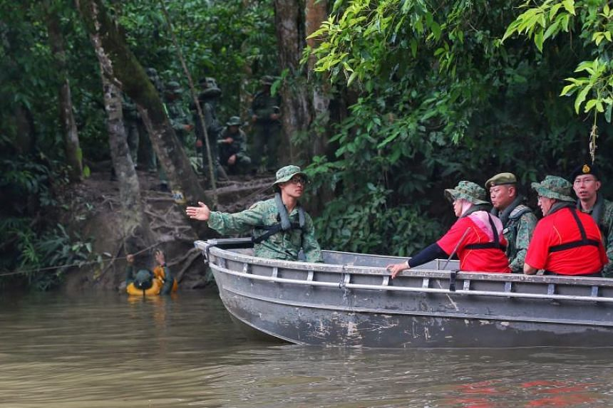 President Halimah Yacob being briefed as SAF officer cadets conduct river crossing training in Temburong.
