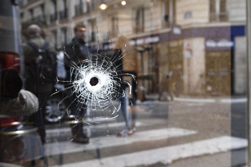 A bullet hole is seen on the window of a cafe located at the crossroads between the streets Saint-Augustin and Monsigny on May 13, 2018 in Paris, the day after a knifeman killed one man and wounded four other people.