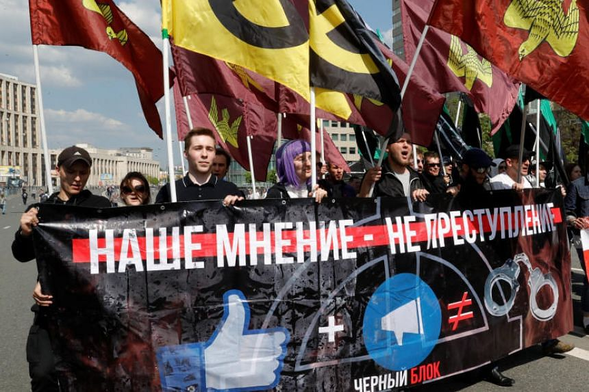 """People hold a banner that reads """"Our opinion is not a crime"""" during a rally in protest against court decision to block the Telegram messenger because it violated Russian regulations, in Moscow, Russia on May 13, 2018."""