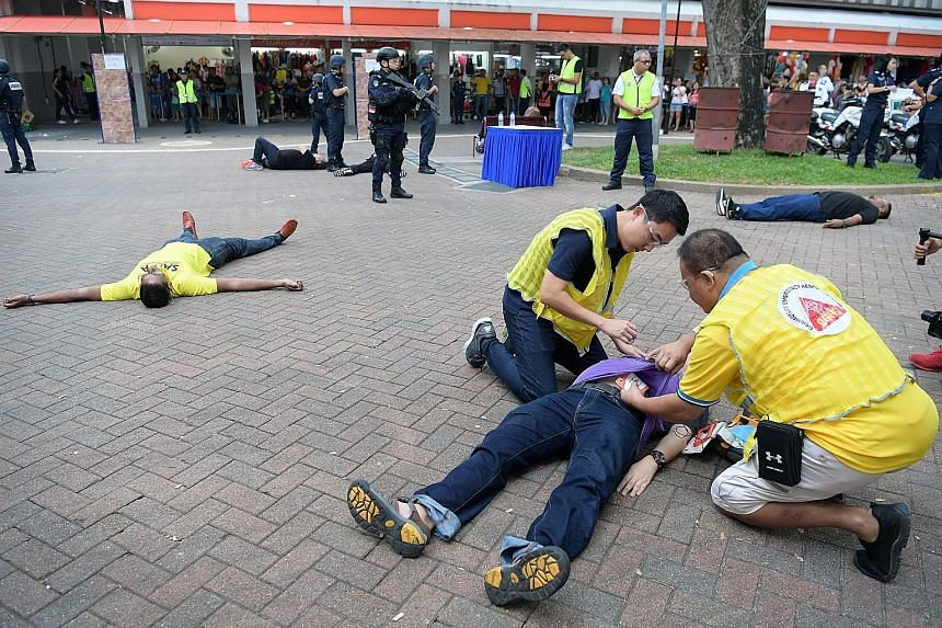 """Members of the Singapore Police Force's Clementi Division Emergency Response Team taking down a """"terrorist"""" at Telok Blangah Emergency Preparedness Day yesterday. More than 1,000 residents of Telok Blangah attended the event, which is part of the SGS"""