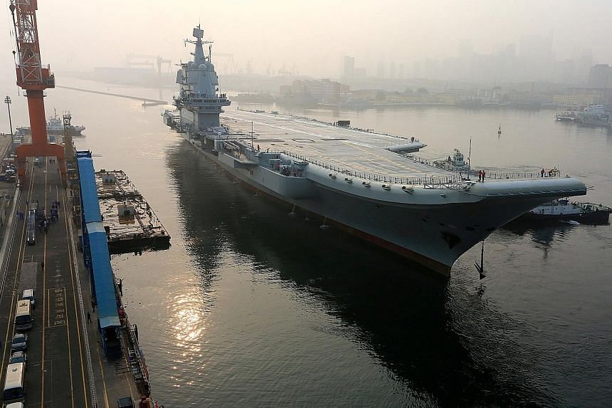 China's first domestically developed aircraft carrier departing Dalian in Liaoning province, China, yesterday for sea trials. It is not expected to enter service until 2020, once it has been fully kitted out and armed.