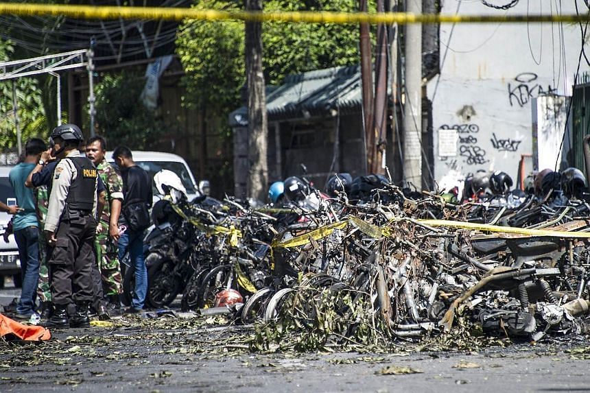 Police and soldiers examining the area after an attack outside the Surabaya Centre Pentecostal Church in East Java yesterday. The attack was one of three carried out by a family on churches in Surabaya. Puji Kuswati, 46, and her family, including her