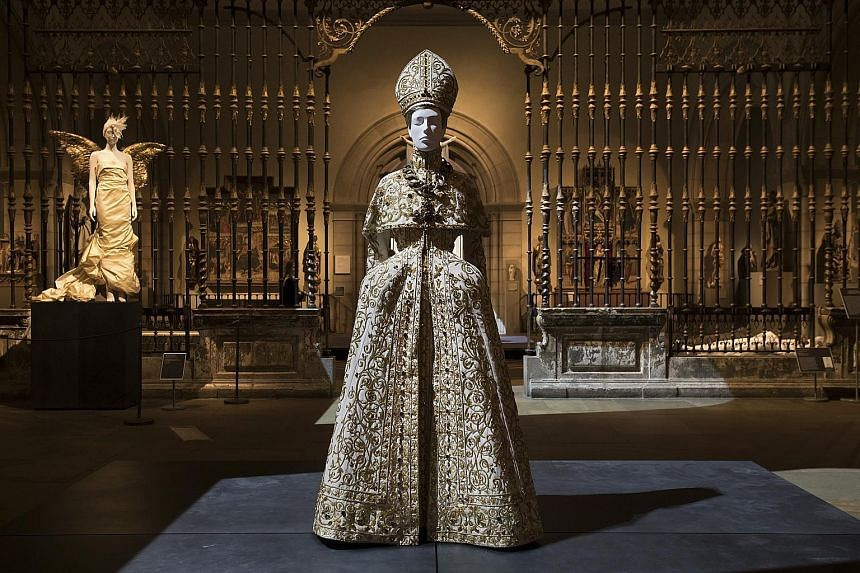 This ornate dress (center) by designer John Galliano for the House of Dior in the early 2000s is one of more than 150 outfits on display at the exhibition, Heavenly Bodies: Fashion And The Catholic Imagination. Organised by curator Andrew Bolton, the