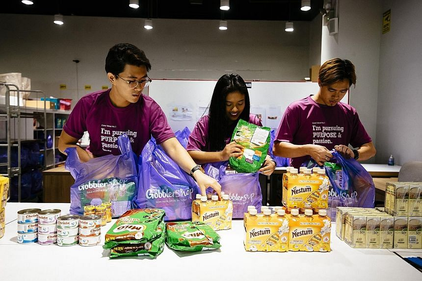 (From left) GobblerCo's corporate relations manager Ephraim Teng, 28, and retail executives Nurul Fatehah, 20, and Sean Soo, 24, packing the bags of groceries for beneficiaries.