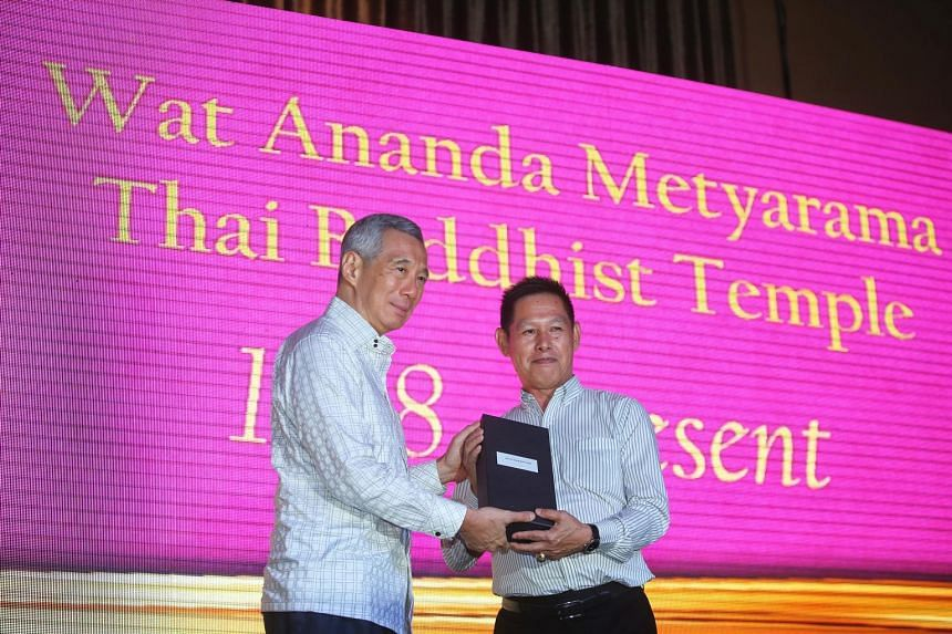 Mr Lim Keng Boon (at right) receiving a long service award yesterday from Prime Minister Lee Hsien Loong at a celebration marking the Wat Ananda Metyarama Thai Buddhist Temple's 100th anniversary.