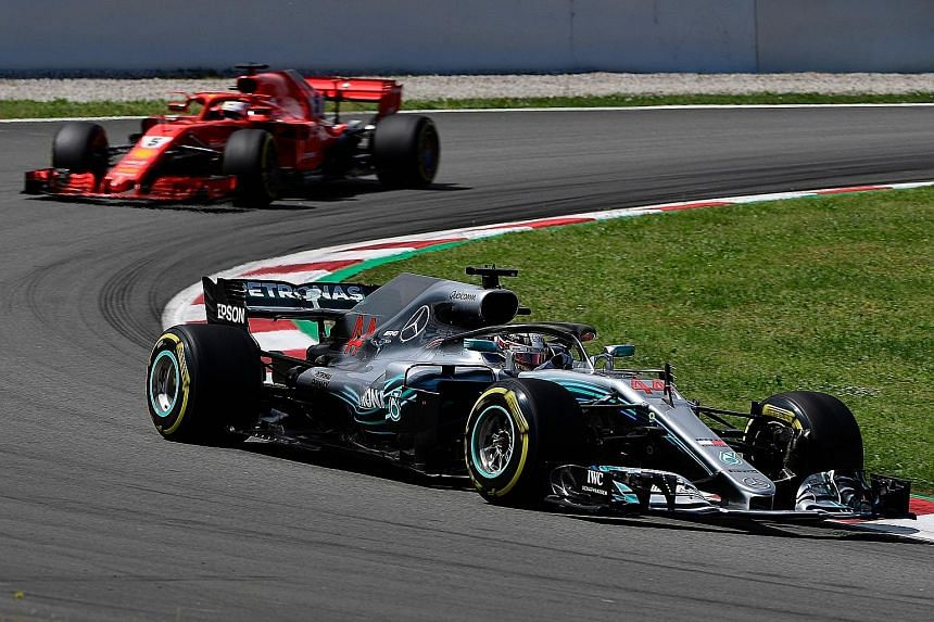 Mercedes' Lewis Hamilton (front) and Ferrari's Sebastian Vettel competing in the Spanish Grand Prix yesterday. Hamilton has a 17-point lead over Vettel following his win.