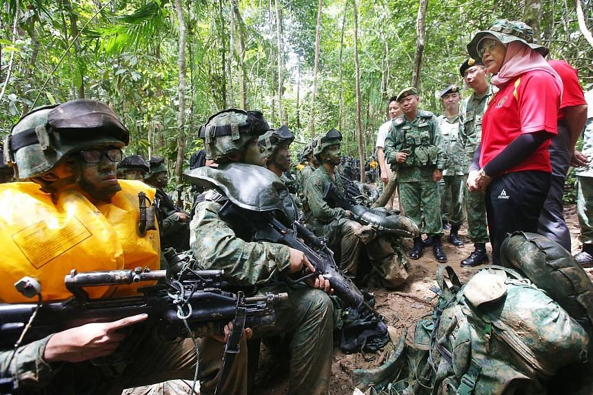 President Halimah Yacob, accompanied by Chief of Army Goh Si Hou (on her right), speaking to SAF officer cadets during their training in Temburong in Brunei yesterday. When she visited the Defence Academy of the Royal Brunei Armed Forces on Saturday,