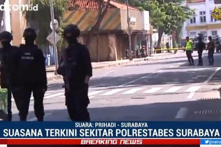 A screengrab of a news report showing officers at the scene of the explosion at Surabaya police headquarters.