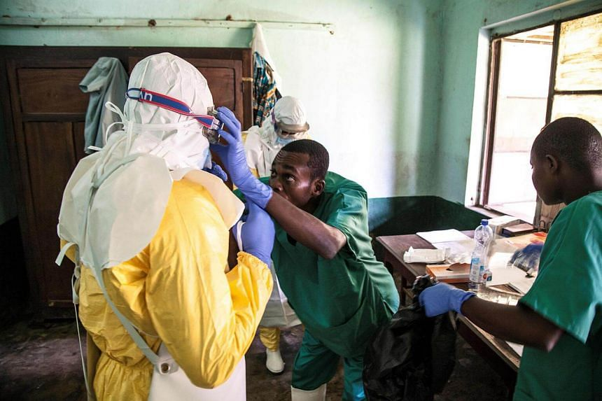Health workers wear protective equipment as they prepare to attend to suspected Ebola patients at Bikoro Hospital on May 12, 2018.