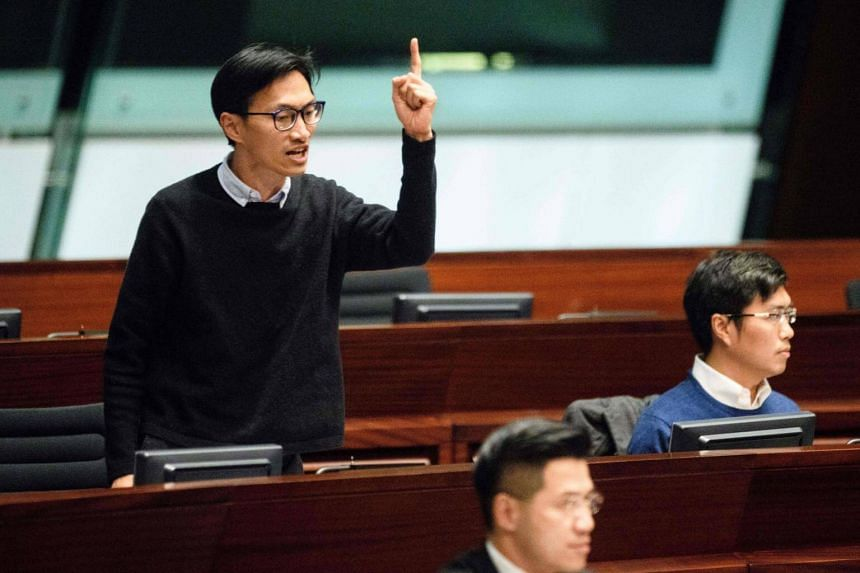 Lawmaker Eddie Chu (left) shouts as newly elected lawmaker Vincent Cheng (not seen) takes the Legislative Council oath in Hong Kong, on March 21, 2018.