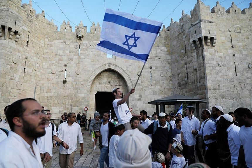 Israelis celebrate as they hold their national flag during a parade marking the annual Jerusalem Day outside the Damascus Gate on May 13, 2018.