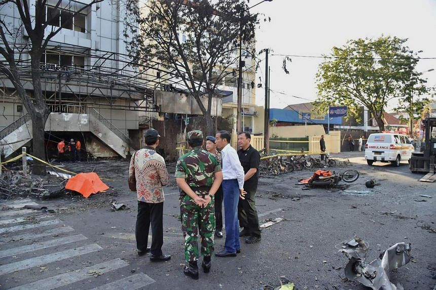 Indonesia's President Joko Widodo (second, right) visiting the scene of a suicide attack outside the Central Pantekosta church in Surabaya.