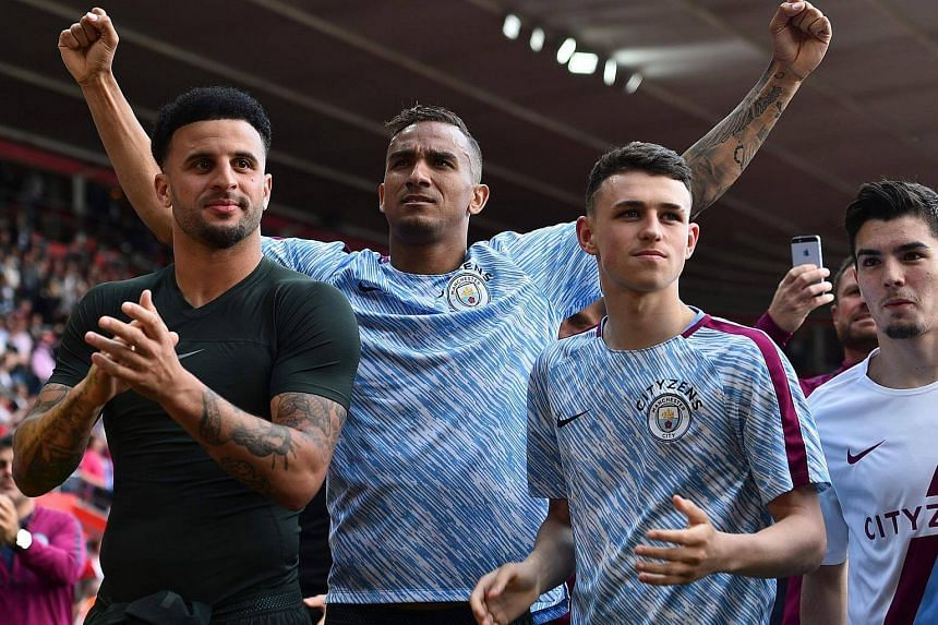 Manchester City's defender Danilo (centre) gestures to the fans behind defender Kyle Walker (left) and midfielder Phil Foden (right) at the end of the English Premier League football match between Southampton and Manchester City, on May 13, 2018.
