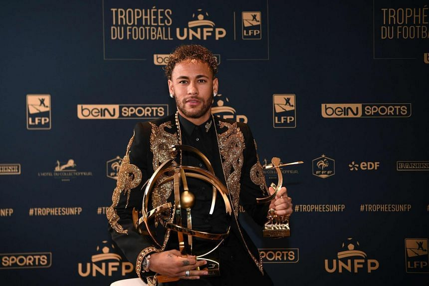 Paris Saint-Germain's Brazilian forward Neymar poses with his trophy after receiving the Best Ligue 1 Player award during a TV show in Paris, on May 13, 2018.