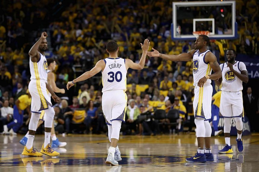 Stephen Curry #30 of the Golden State Warriors is congratulated by his teammates after he made a basket during Game Five of the Western Conference Semifinals of the 2018 NBA Playoffs, on May 8, 2018.